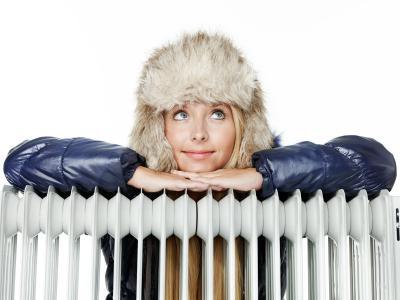 Frau spart Heizkosten durch dicke Wintersachen