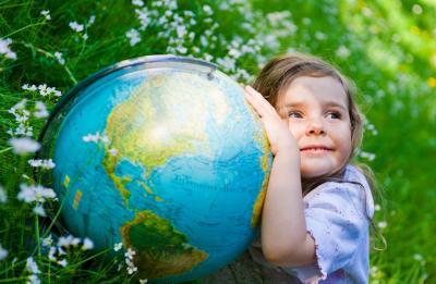 Mädchen profitiert von umweltbewusstem Heizen und umarmt Weltkugel